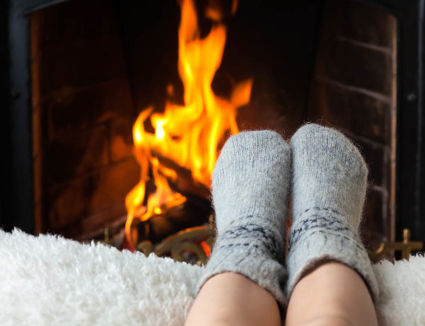 Children's feet in warm woolen socks heated in the fire in the fireplace